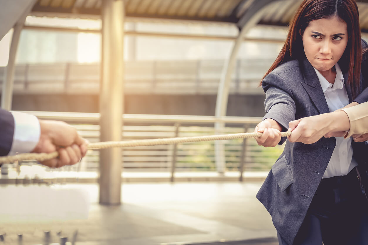 Business women help pull the rope against the business man