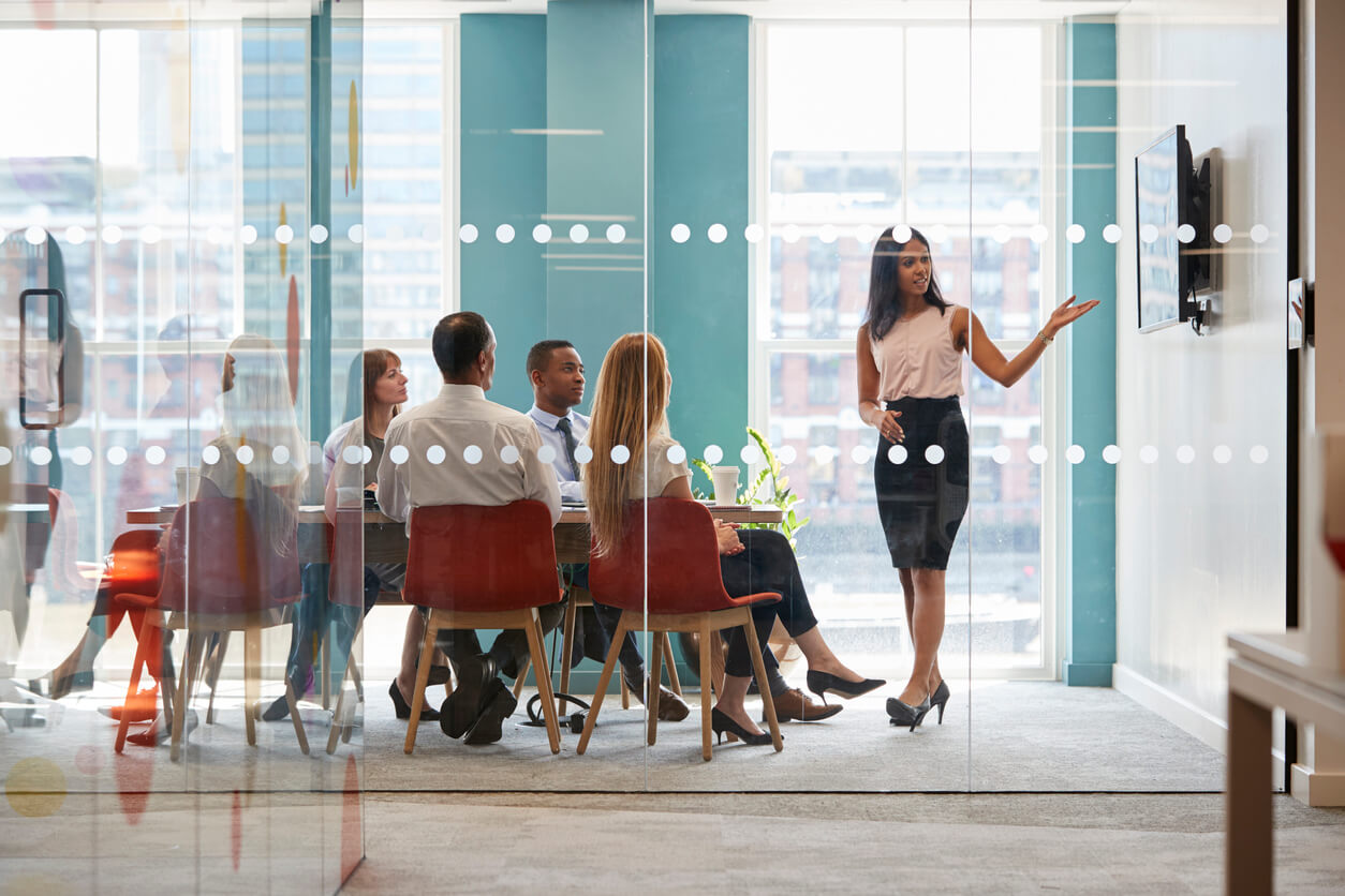 woman giving presentation in glass walled office