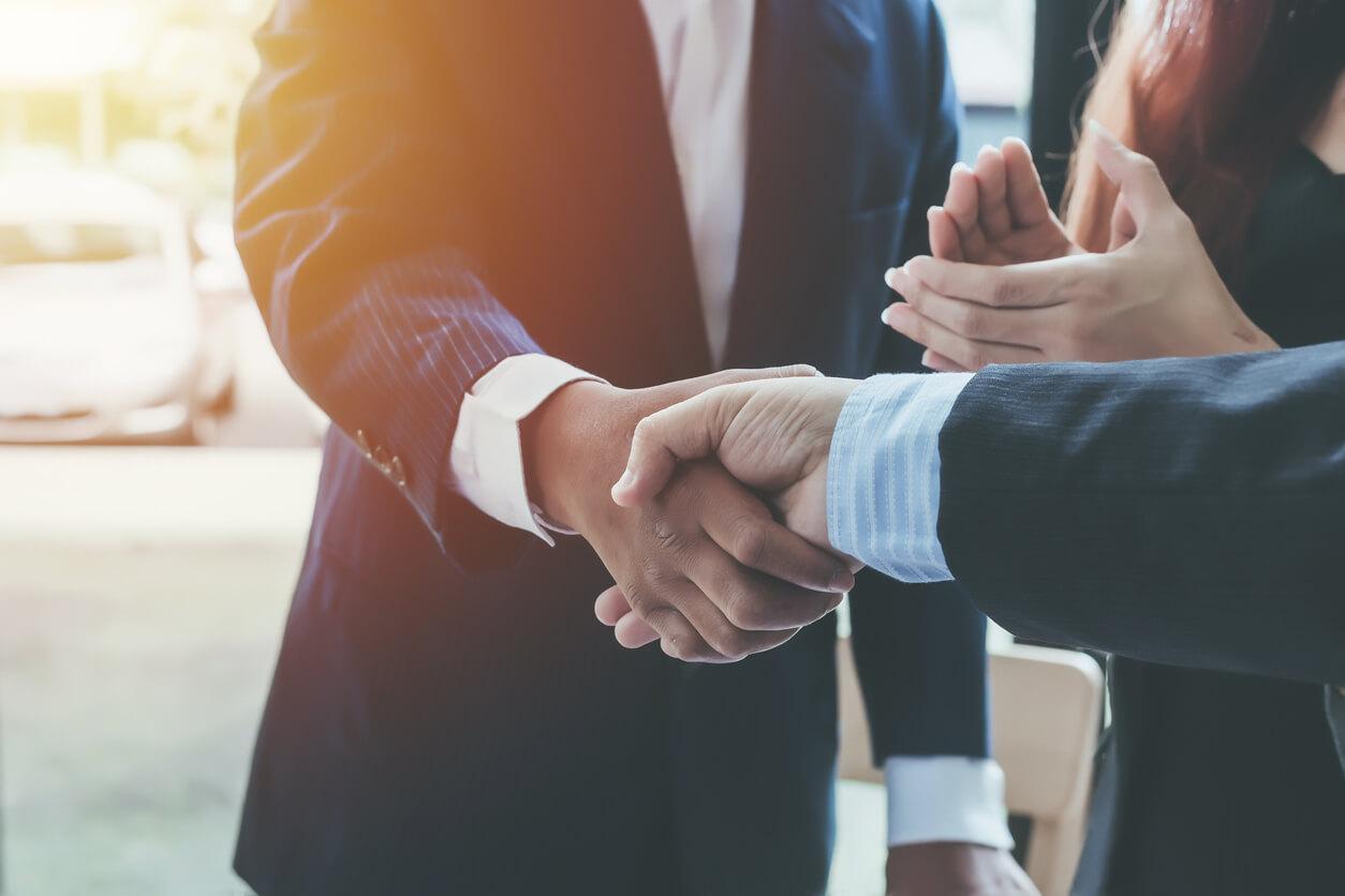 men in suits shaking hands closeup
