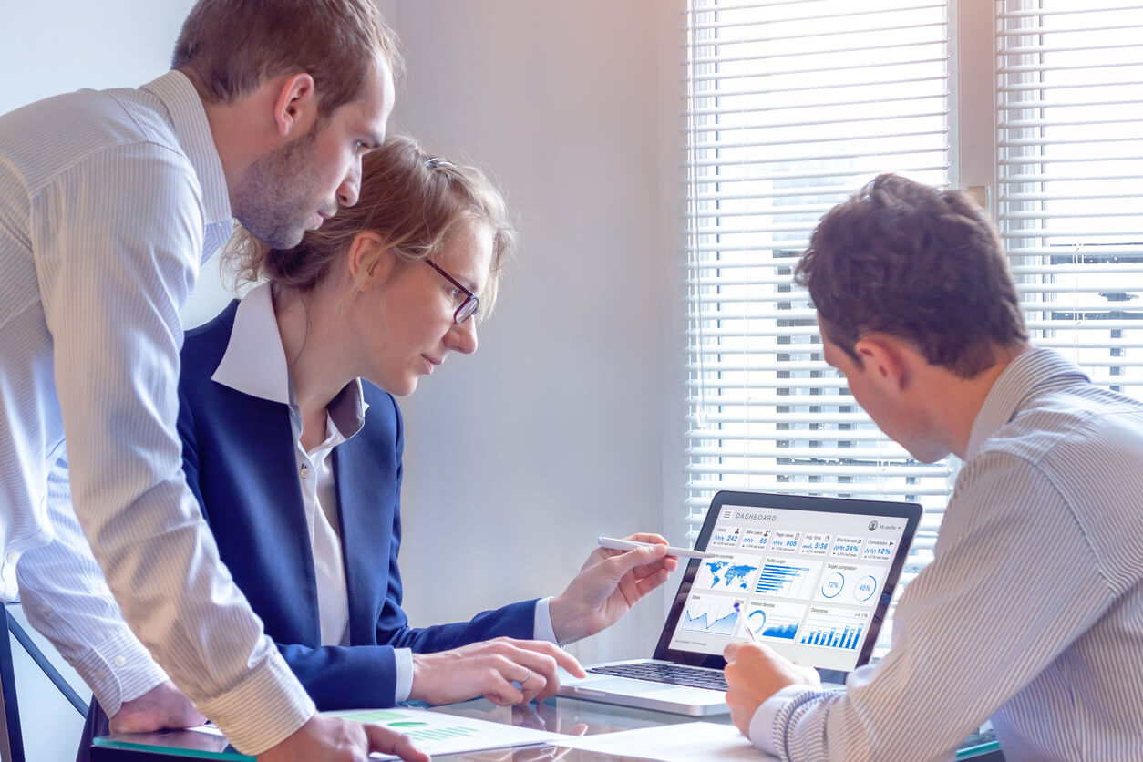 Digital marketers working on internet advertisement campaign analytics data on KPIs
