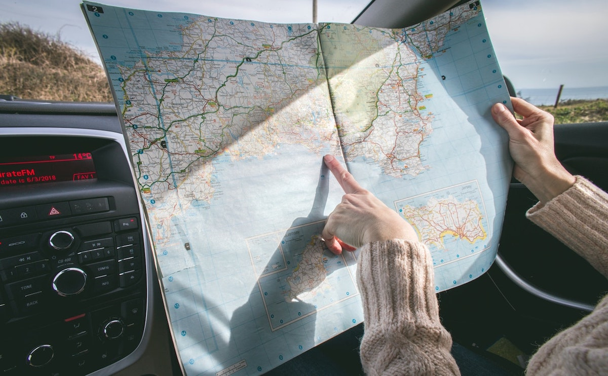 person-wearing-beige-sweater-holding-map-inside-vehicle-1252500
