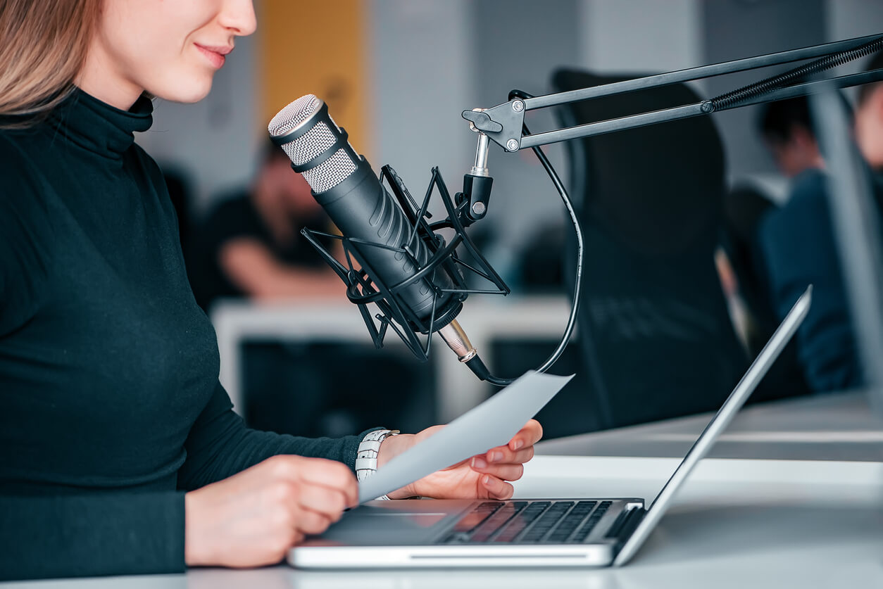 Young woman recording a podcast in a studio