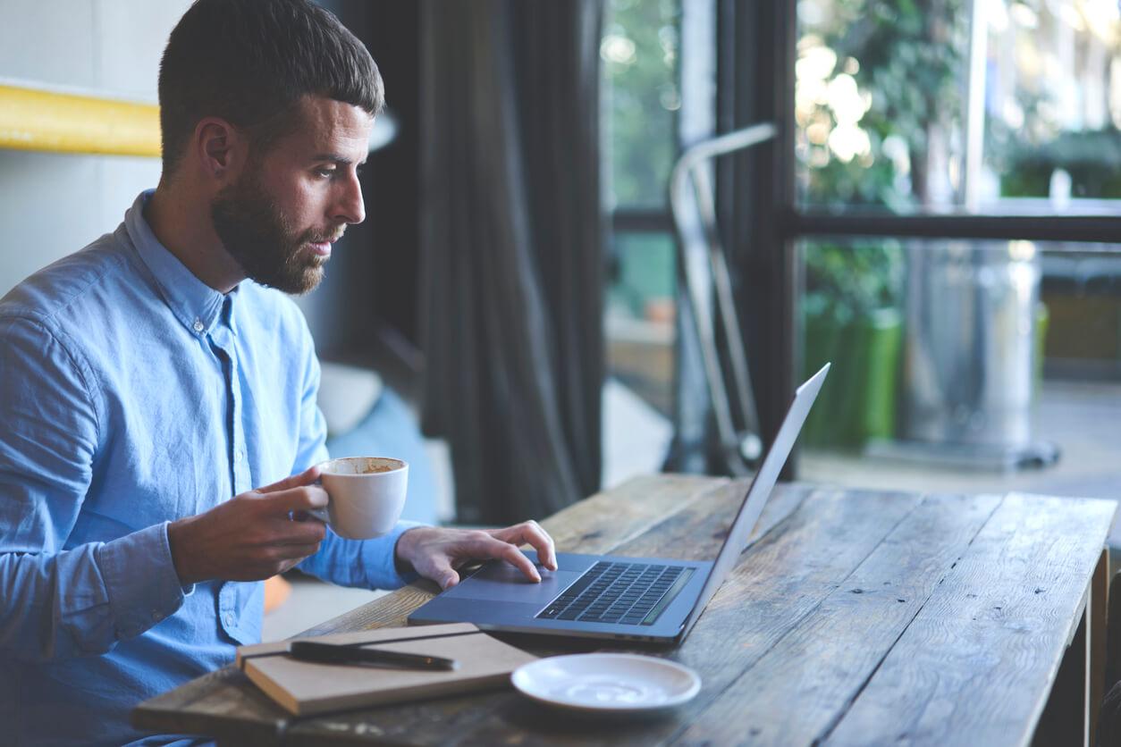 man focused on laptop holding mug