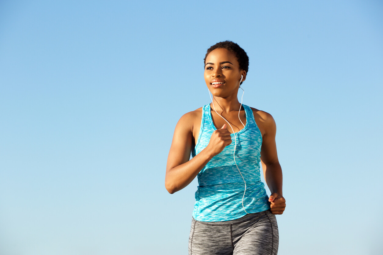 woman running with headphones in front of blue sky