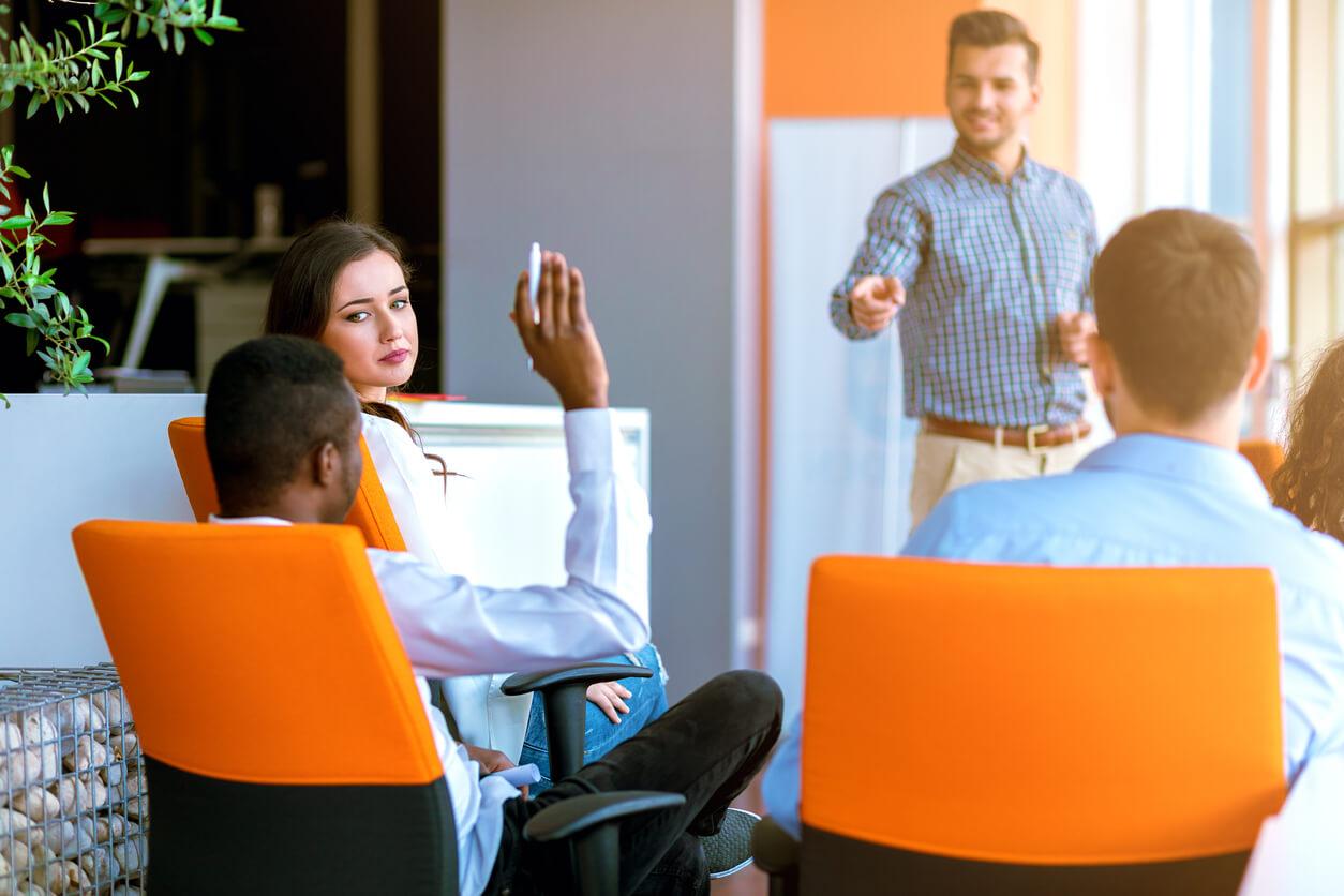 man raising hand with orange chairs