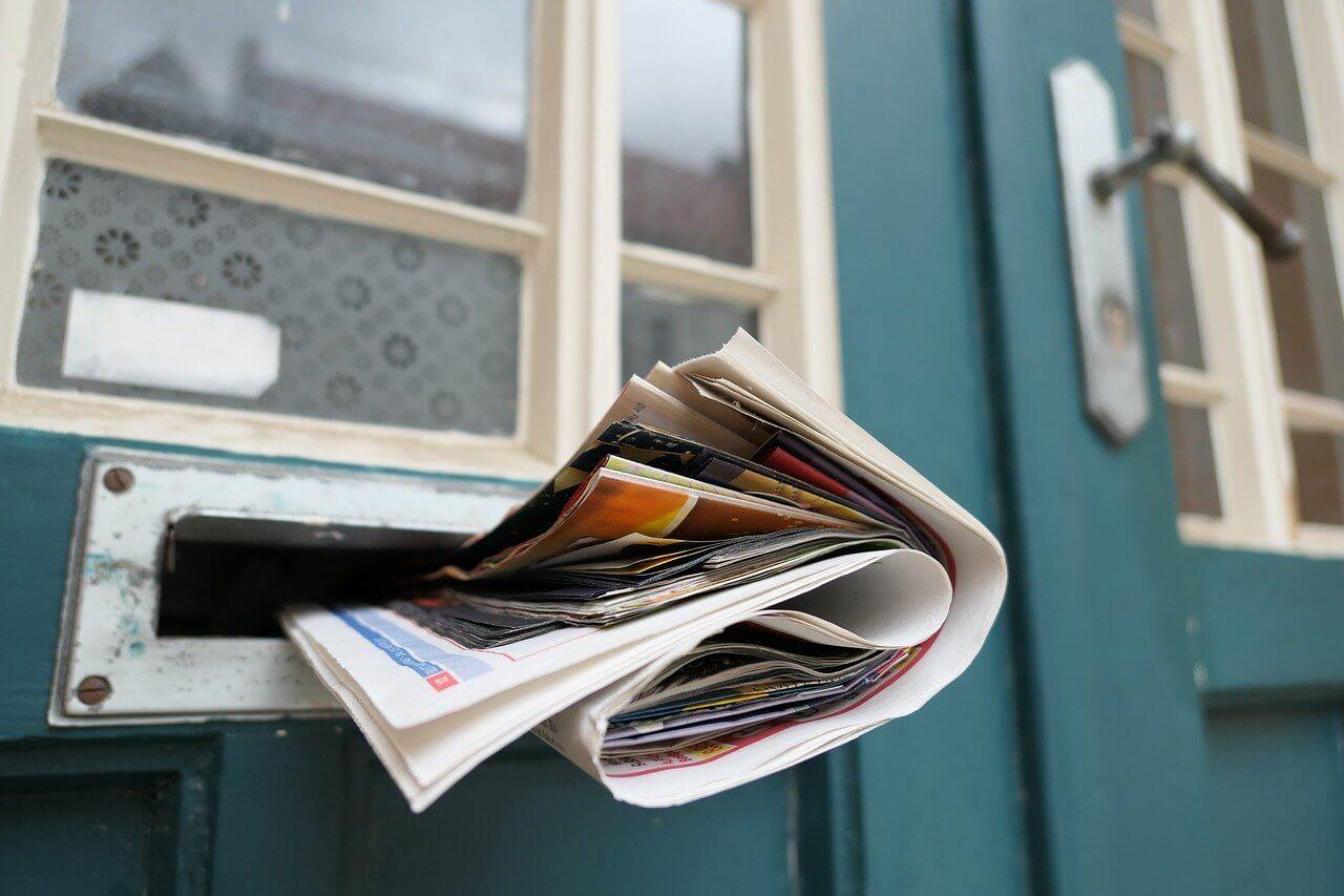 newspaper stuffed in mailbox