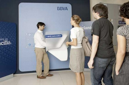 BBVA's next-generation ATMs. Customers stand at 90° to people waiting in the queue, shielded by a frosted panel.